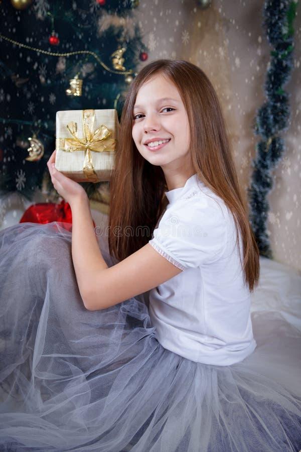 Girl holding gift box under Christmas tree royalty free stock photos