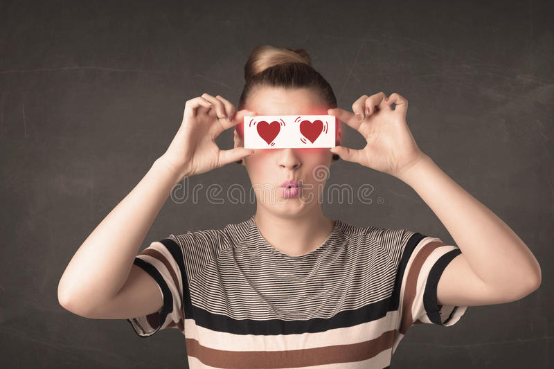 Pretty girl holding paper with red heart drawing. Concept royalty free stock images