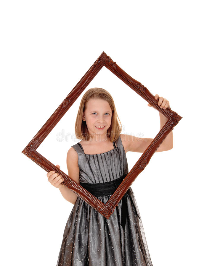 Pretty girl holding picture frame. A lovely young girl in a grey dress holding a picture frame in front of her, isolated on white background royalty free stock photography