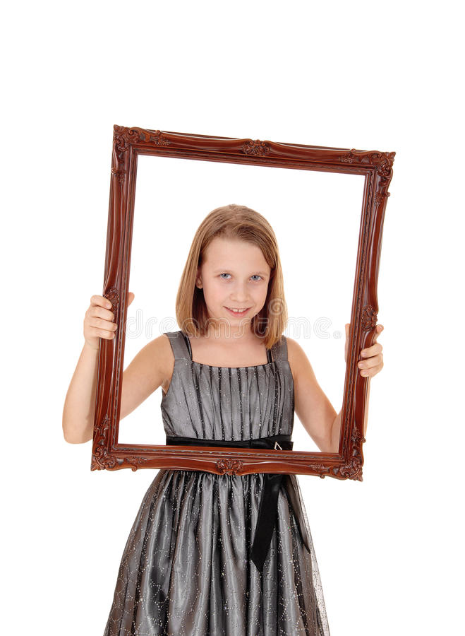 Pretty girl holding picture frame. A lovely young girl in a grey dress holding a picture frame in front of her, isolated on white background royalty free stock photo