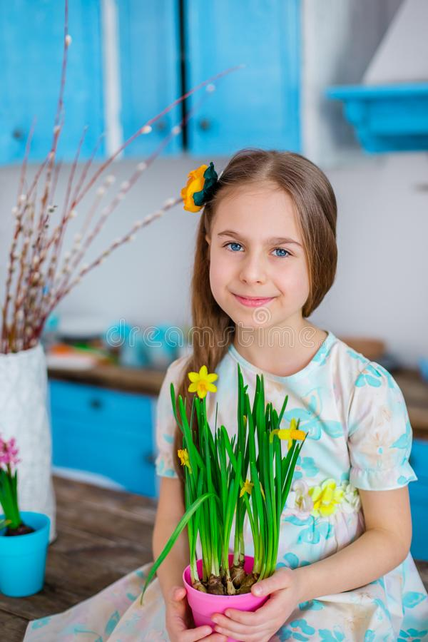 Pretty girl holding a pot of daffodil flowers in anticipation of spring and Easter. Festive mood royalty free stock image