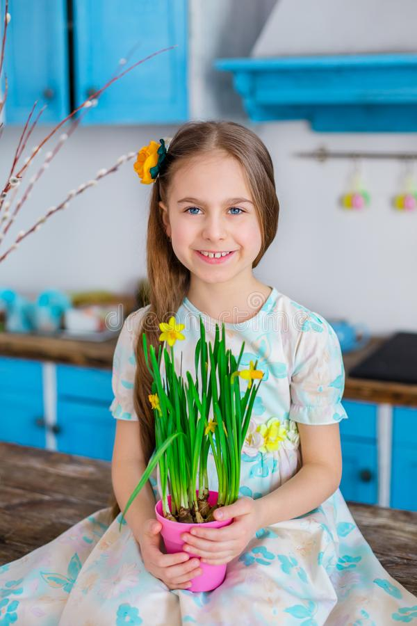 Pretty girl holding a pot of daffodil flowers in anticipation of spring and Easter stock photos