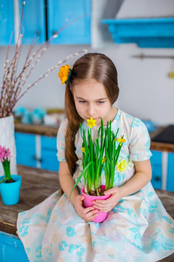 Pretty girl holding a pot of daffodil flowers in anticipation of spring and Easter. Festive mood stock photography
