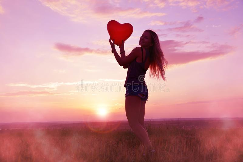 Pretty girl holding red balloon in the shape heart in hands. royalty free stock photography