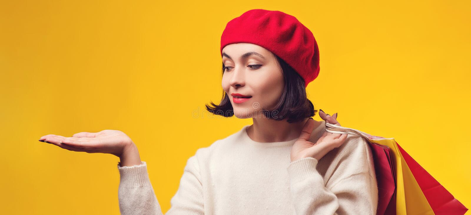 Pretty girl holding shopping bags. Woman in red hat with presentation. Girl showing your product with open hand palm. Shopping stock photography