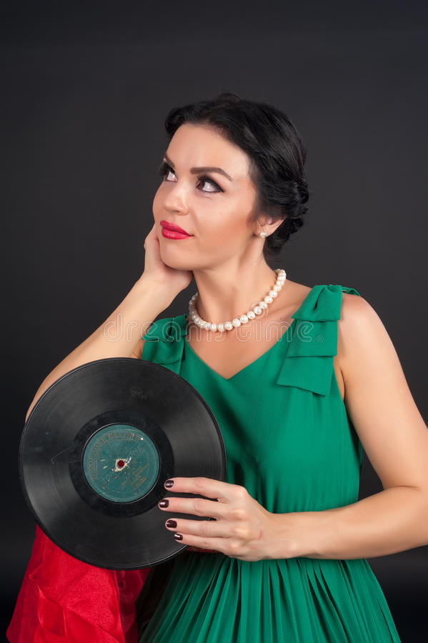Pretty girl holding vinyl disc. Young beautiful woman holding musical disc at black background royalty free stock image