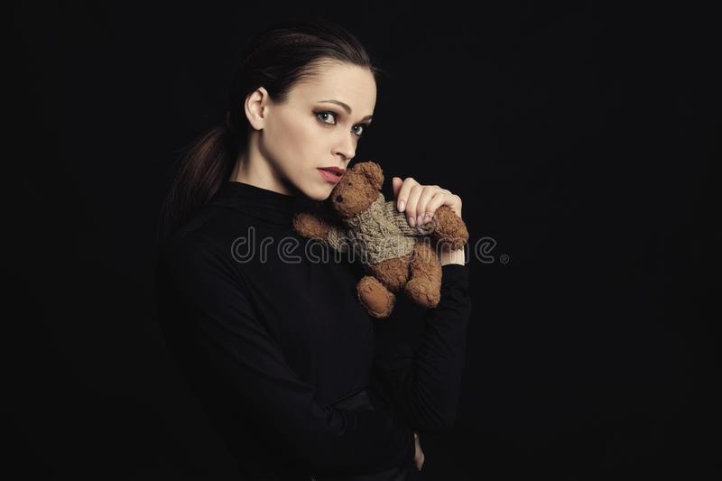 Pretty girl holds a teddy bear over black. Studio background stock photos