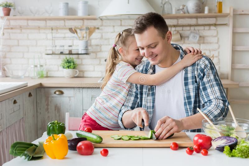 Pretty girl hugging dad while man cooking healthy dinner. I love you, daddy. Pretty girl hugging dad while men cooking healthy dinner, copy space stock photo
