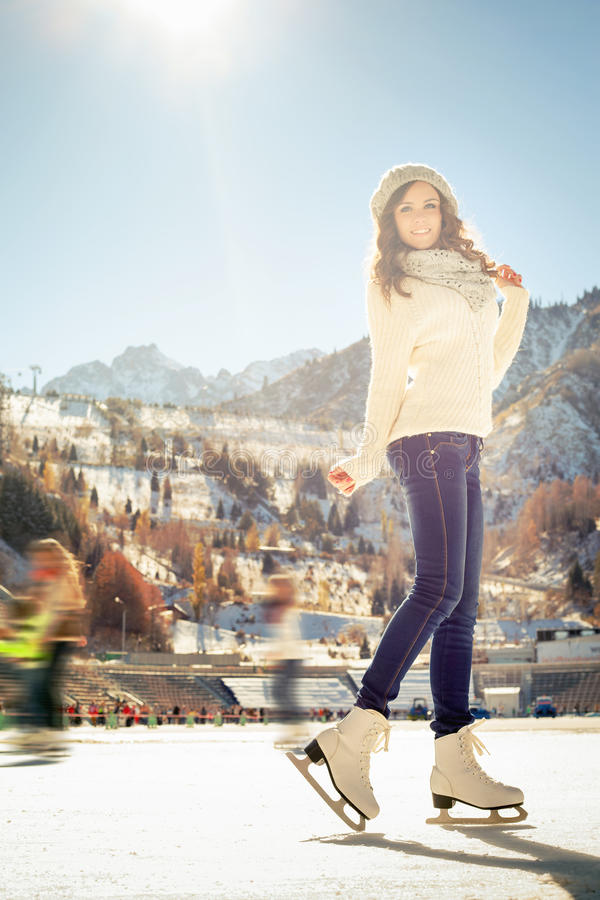Pretty girl ice skating outdoor at ice rink. Young girl teenager elegantly posing and skating at the ice rink outdoor. Medeo stadium. Almaty. Winter activities stock photography