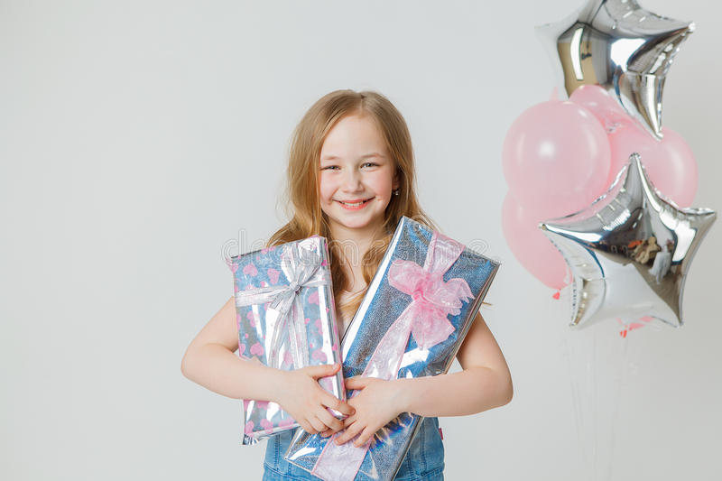 Pretty girl in jeans jacket holding presents in studio. Balloons on background royalty free stock images