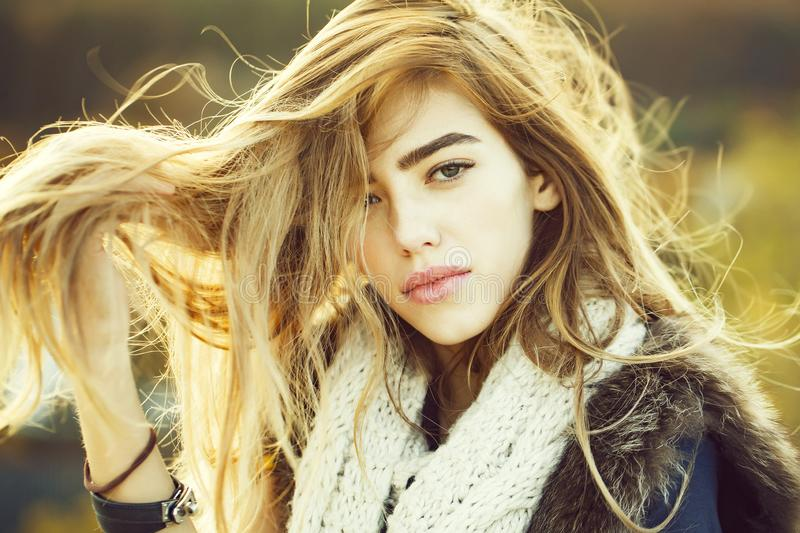 Pretty girl with knitted scarf. Pretty girl young cute woman with long hair in fashionable knitted scarf sunny outdoor on blurred or defocused natural background royalty free stock images