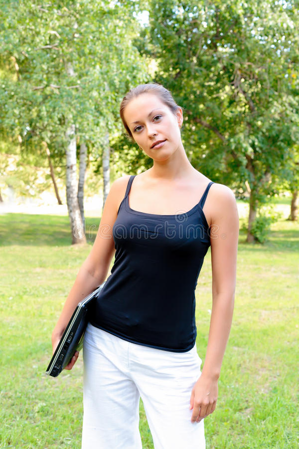 Pretty girl with laptop under her arm stock image