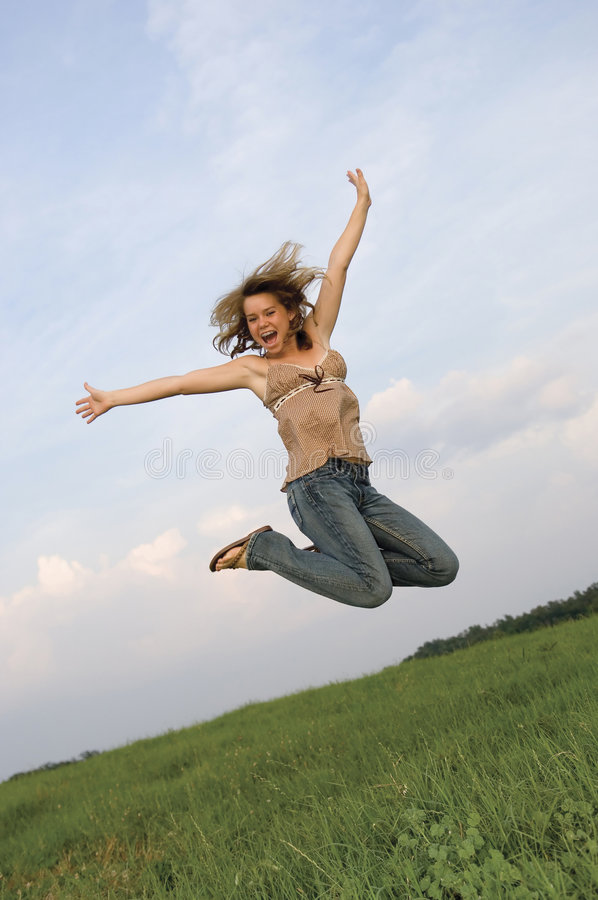 Pretty Girl Leaping in Field stock images