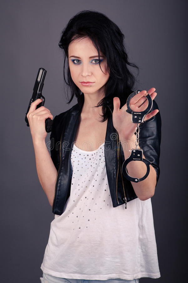 Pretty girl in leather jacket with gun and handcuffs in hand stock images
