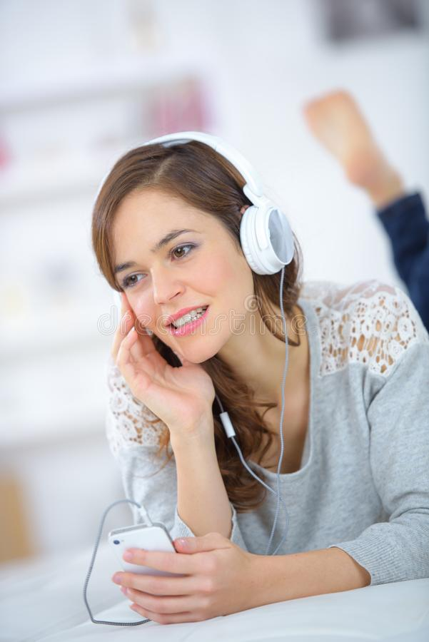 Pretty girl listening to music with headphones in bed stock photography