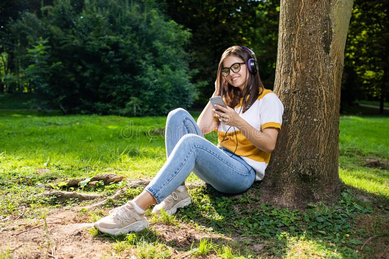 Pretty Girl Listening to the Music in Park royalty free stock image
