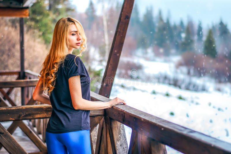 Pretty girl with long curly hair standing on a wooden terrace of a country house royalty free stock photos