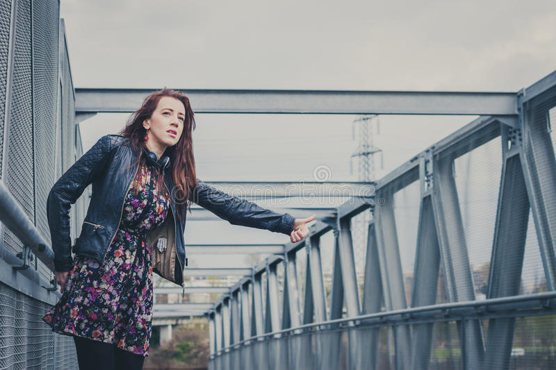 Pretty girl with long hair hitchhiking on a bridge. Pretty girl with long hair and black leather jacket hitchhiking on a bridge royalty free stock photography
