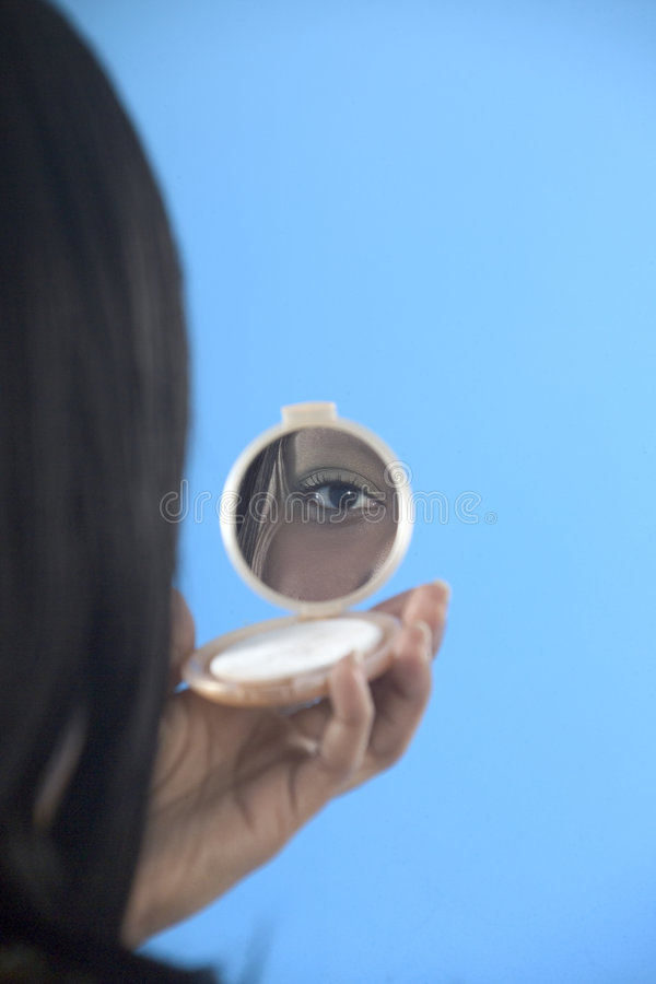 Pretty girl looking in a make up mirror stock photography