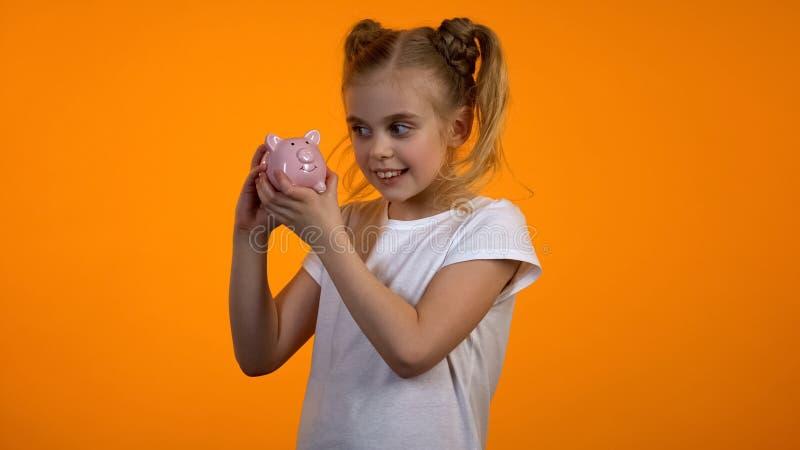 Pretty girl looking at piggybank, financial literacy, savings for future deposit. Stock photo stock photo