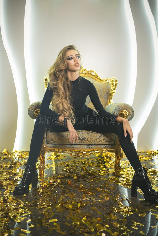 Pretty girl with makeup, long hair, hairstyle, beauty salon. Woman relax in armchair on golden confetti. Fashion, style, lifestyle. Beauty, look, make up Party royalty free stock images