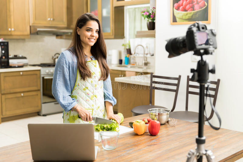 Pretty girl making video for a food blog stock photography