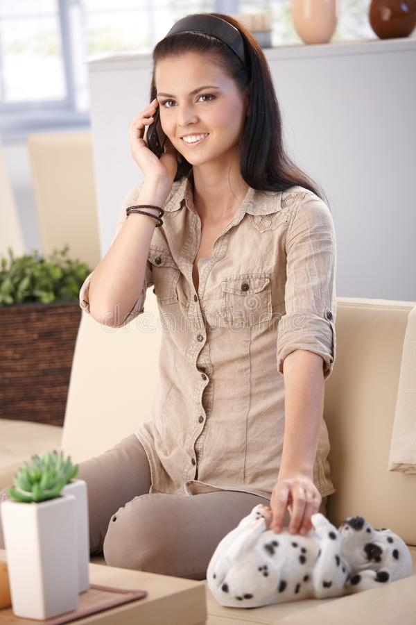 Pretty Girl On Mobile At Home Smiling Royalty Free Stock Photography