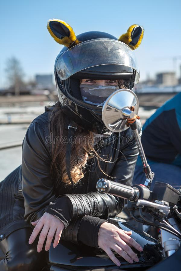 Pretty girl motorcyclist looks at mirror of motorbike, girl dressed in black leather jacket and helmet with yellow funny ears royalty free stock photos