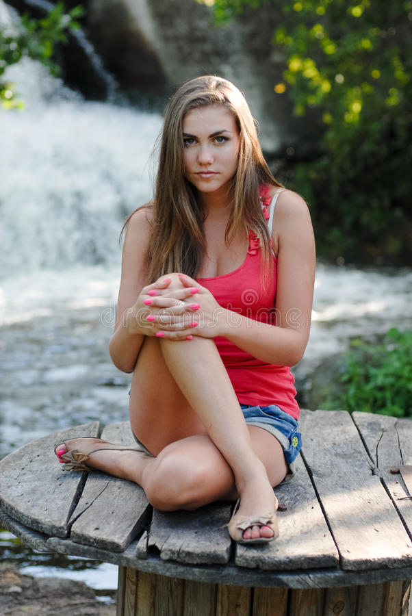 Young woman near waterfall. Pretty girl near waterfall in summer outdoors royalty free stock photo