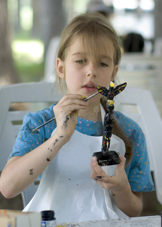 Pretty girl painting totem stock photography