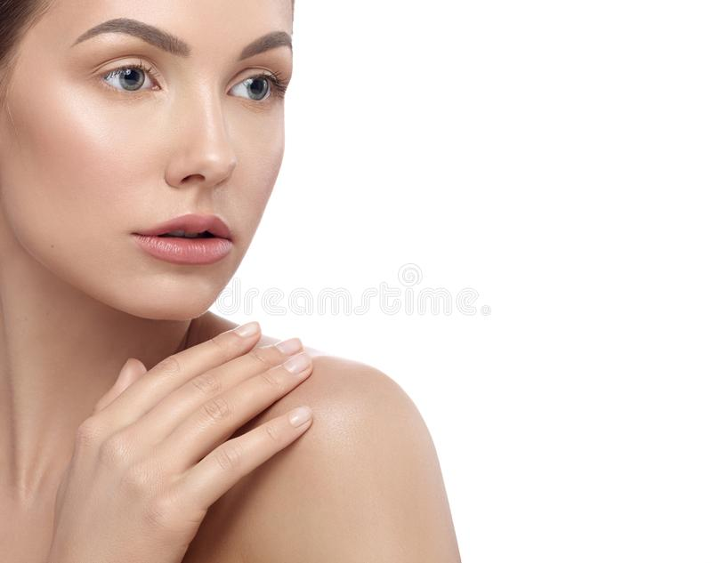Pretty girl with perfect face features touching her shoulder. royalty free stock photos