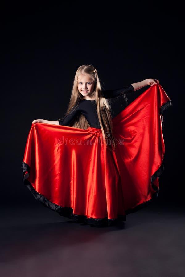 Pretty girl performing hispanic dance in dark royalty free stock image