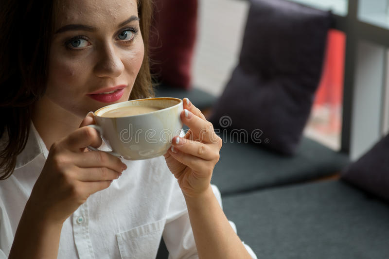 Pretty girl with a pimply face enjoys a fragrant coffee sitting in coffee house. Business woman resting during break royalty free stock photography
