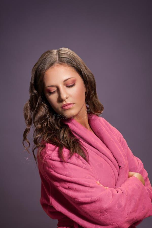 Pretty girl in pink bathrobe royalty free stock photography