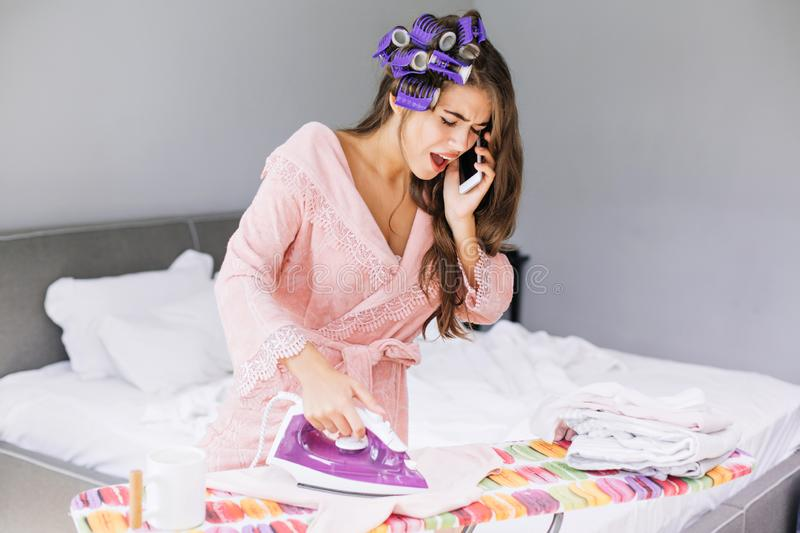 Pretty girl in pink bathrobe and curler ironing clothes and speaking on phone at home. She looks astonished and busy. Pretty girl in pink bathrobe and curler royalty free stock image