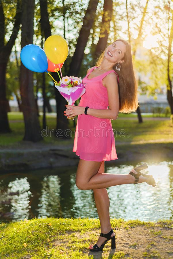 Pretty girl in pink dress with flowers and balloons royalty free stock images