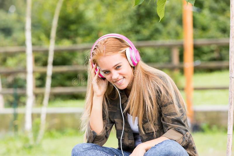 Pretty girl with pink headphones. Listening to her favourite music on her favorite mobile device, maybe a mobile phone royalty free stock image