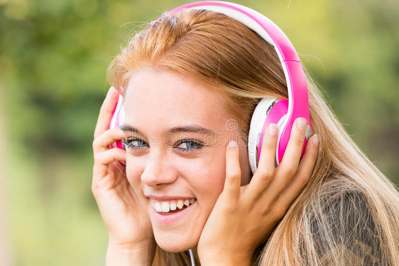 Pretty girl with pink headphones. Listening to her favourite music on her favorite mobile device, maybe a mobile phone royalty free stock photo