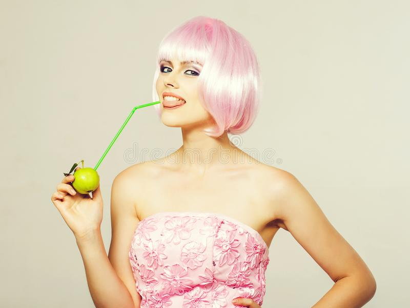 Pretty girl in pink wig with green apple stock image