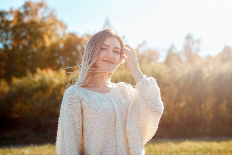 Pretty girl posing on camera and enjoying sunny autumn day. royalty free stock photo