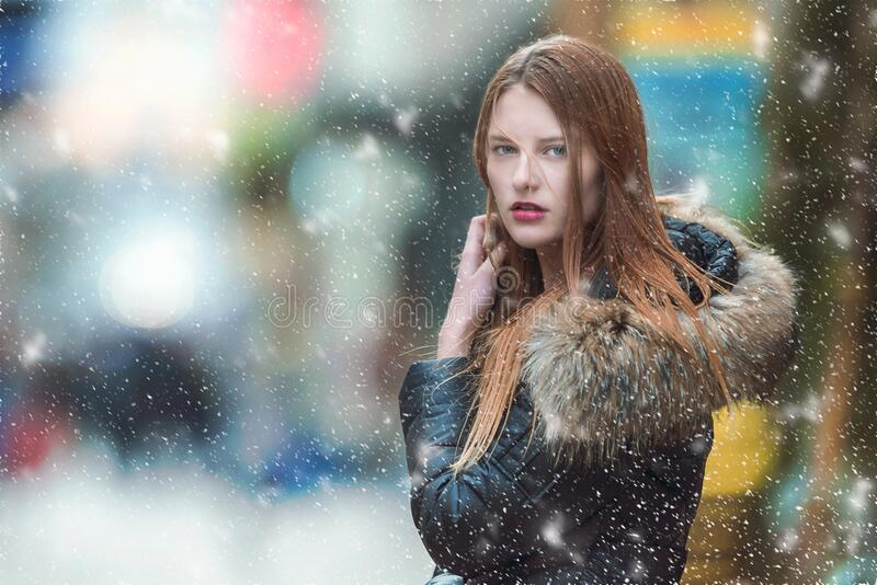 Pretty girl posing in the snow stock photos