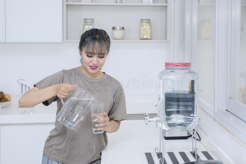 Pretty girl pouring fresh water at home stock photo