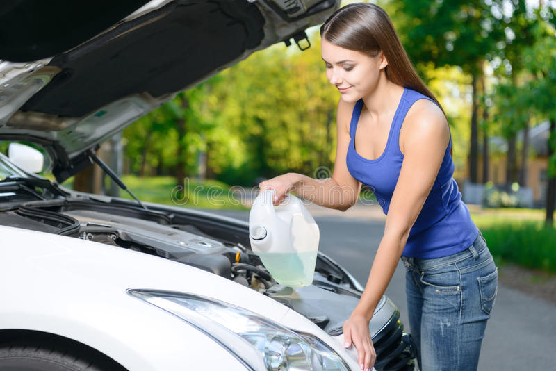 Pretty girl pouring liquid for car royalty free stock photography