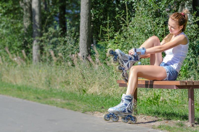 Pretty girl putting on inline skates. Pretty girl sitting on the bench and putting on inline skates stock photo