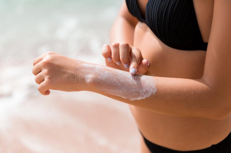 Pretty girl is putting sun lotion on her hand at the beach royalty free stock images