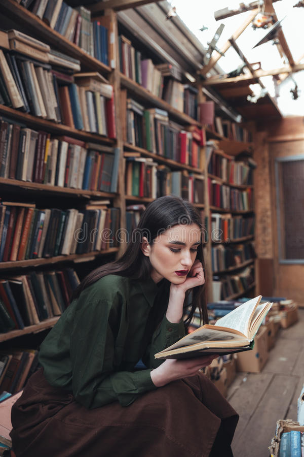 Pretty girl reading book in library stock photography