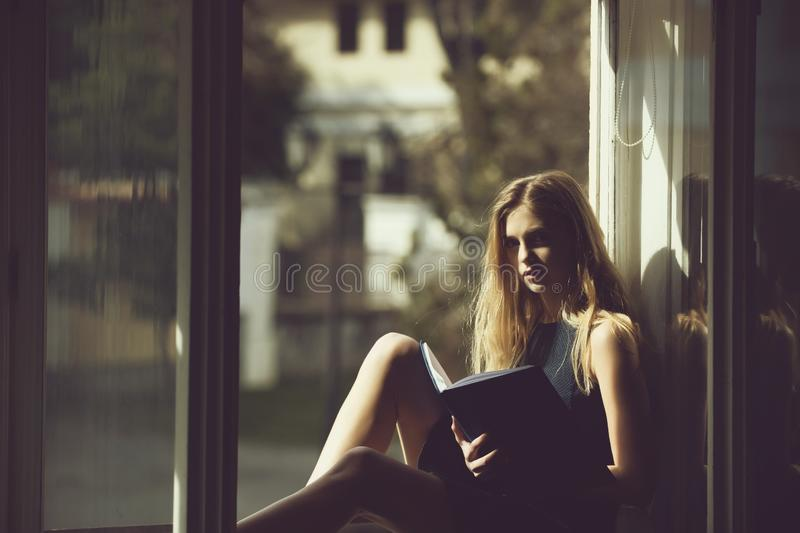 Pretty girl reading book on window sill royalty free stock photos