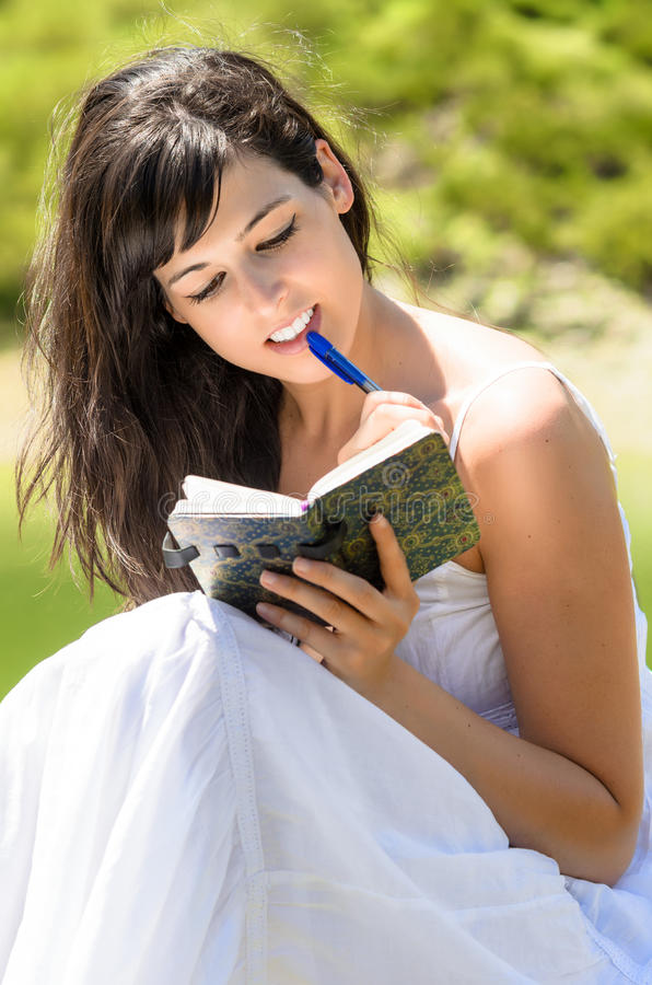 Pretty girl reading and writing in her diary stock images