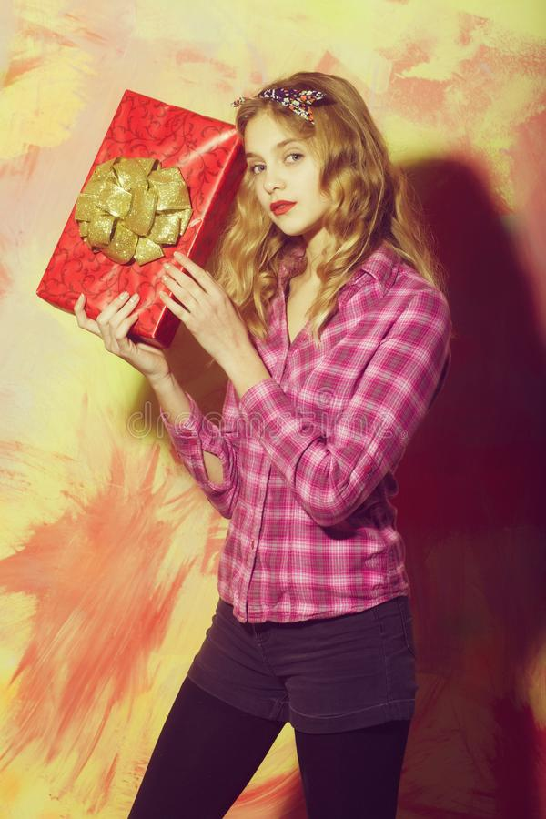 Pretty girl with red gift box with golden bow royalty free stock photo