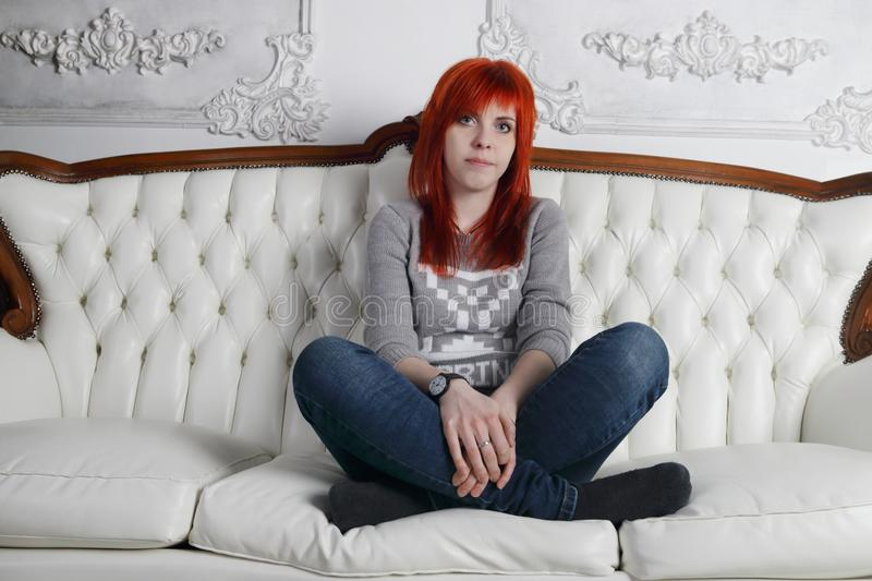 Pretty girl with red hair squats crosslegged. On white sofa in white room stock images